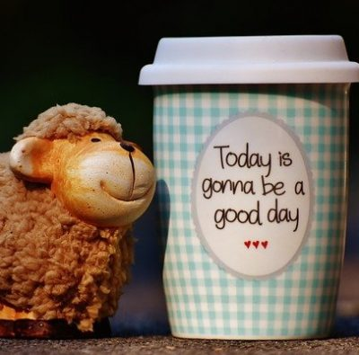 """Happy sheep figurine next to coffee cup """"Today is gonna be a good day"""""""